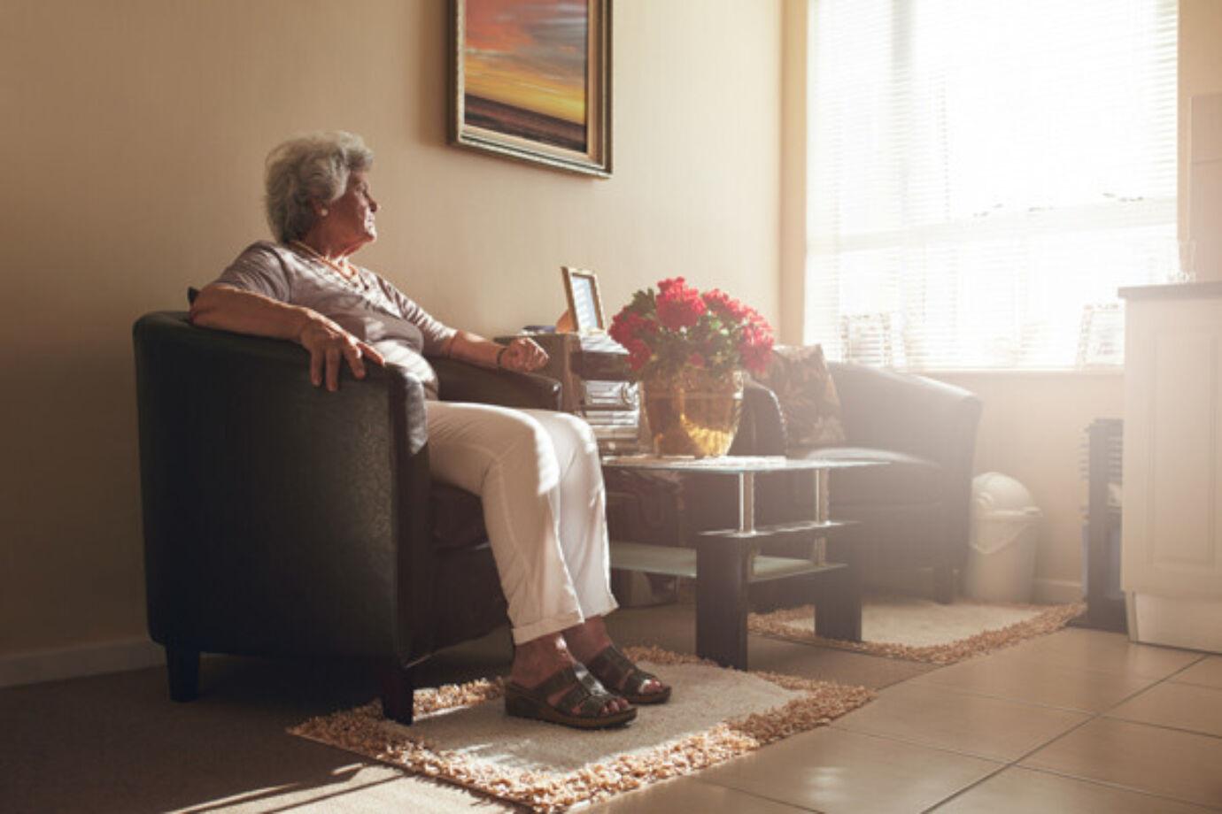 Oudere vrouw door het raam aan het kijken vanuit haar kamer