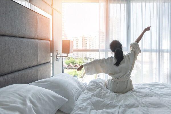 vrouw die wakker wordt in kamer met veel licht