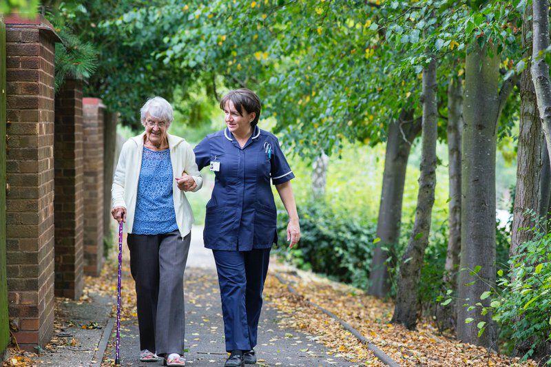 Oudere dame aan het wandelen met zorgverlener woonzorgcentra