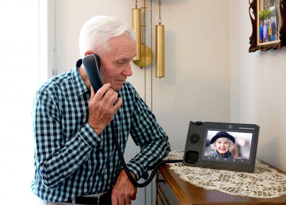 Oudere man aan het bellen met de zorgtelefoon